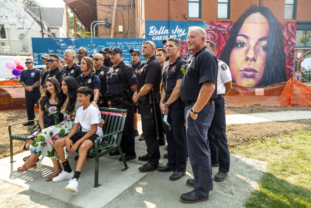 Isabella Thallas' family poses for a picture with members of Denver's police and fire departments as Bella Joy Gardens is christened. Aug. 22, 2020.