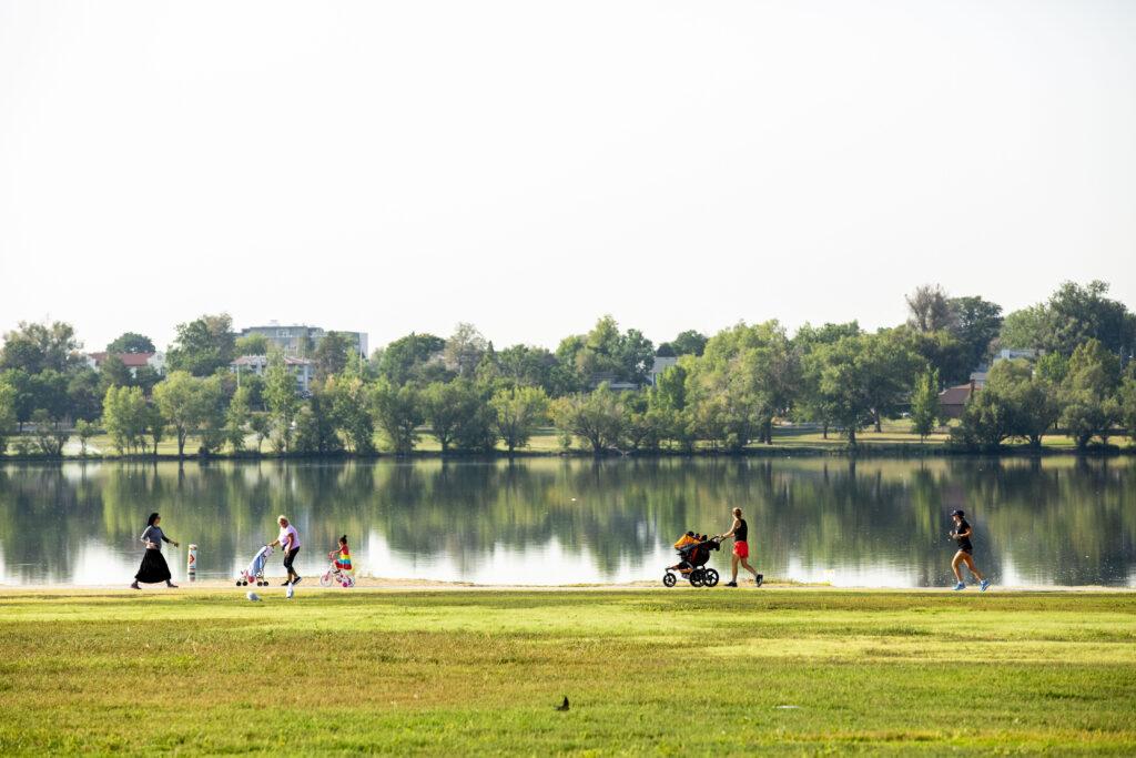 Humans move around the edge of Sloan's Lake. Aug. 20, 2020.