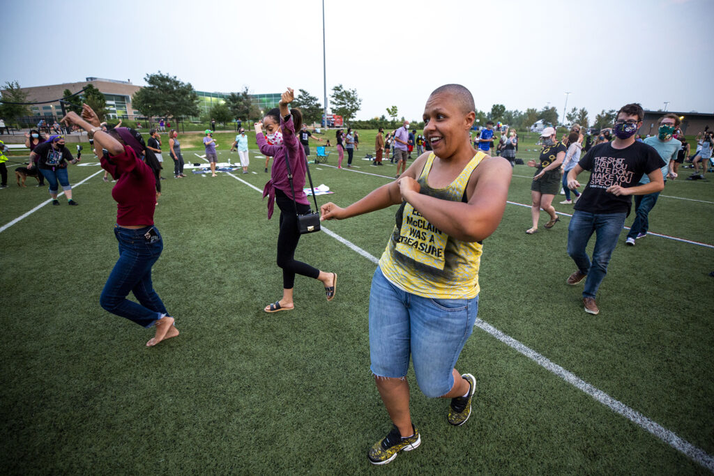 Candace Bailey, an organizer of a gathering to remember Elijah McClain, gets down with the crowd at the Montbello Rec Center. Aug. 23, 2020.