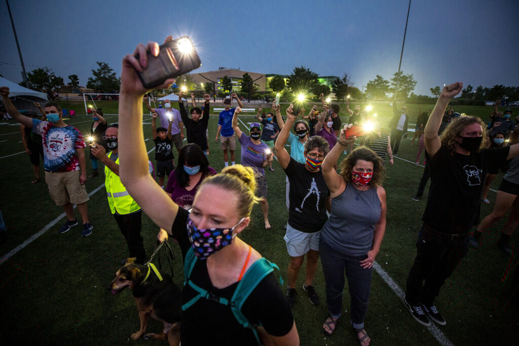 The crowd holds up lights and fists as Elijah McClain and Breonna Taylor's names are chanted during a gathering in their honor at the Montbello Rec Center. Aug. 23, 2020.