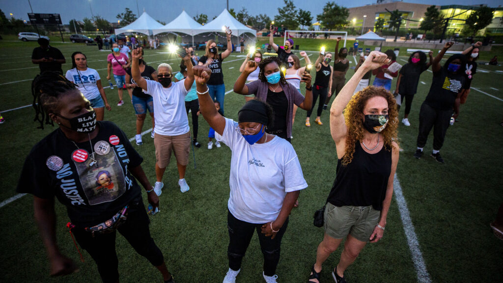 Sheneen McClain holds up a fist during a gathering at the Montbello Rec Center in honor of her son, Elijah. Aug. 23, 2020.