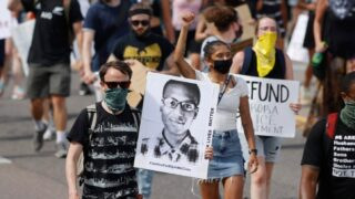 Demonstrators carry placards as they walk down Sable Boulevard during a rally and march over the death of 23-year-old Elijah McClain, Saturday, June 27, 2020, in Aurora, Colo. McClain died in late August 2019 after he was stopped while walking to his apartment by three Aurora Police Department officers.