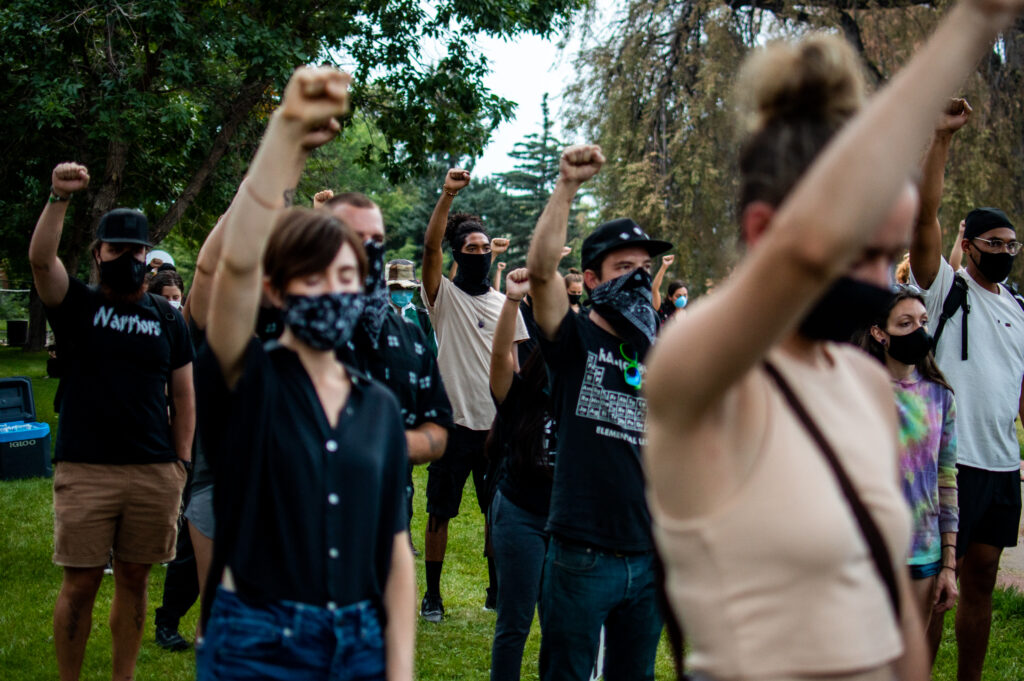 """Attendees raise their fists in solidarity during the """"Protect Black Men: Colorado Action for Jacob Blake"""" gathering at Manual High School in Denver."""