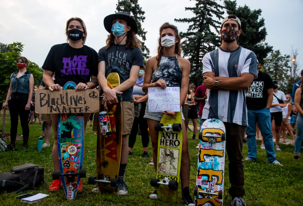"""From left, Lexie Sievert, Luke Foltz, Arianna Schwab and Teagan Glass hold their signs and skateboards during the """"Protect Black Men: Colorado Action for Jacob Blake"""" gathering at Manual High School in Denver."""