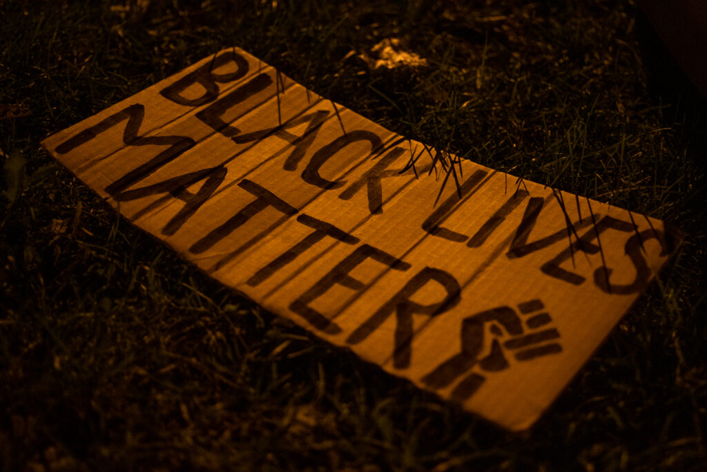 """A Black Lives Matter sign rests on the grass after the """"Protect Black Men: Colorado Action for Jacob Blake"""" gathering at Manual High School in Denver."""
