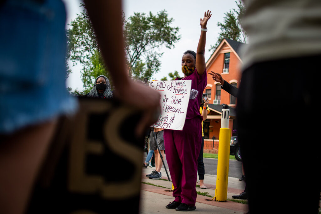 """MiDian Holmes raises her hand when a speaker asks who has had a gun pointed at them by police. Holmes was attending the """"Protect Black Men: Colorado Action for Jacob Blake"""" gathering at Manual High School in Denver."""