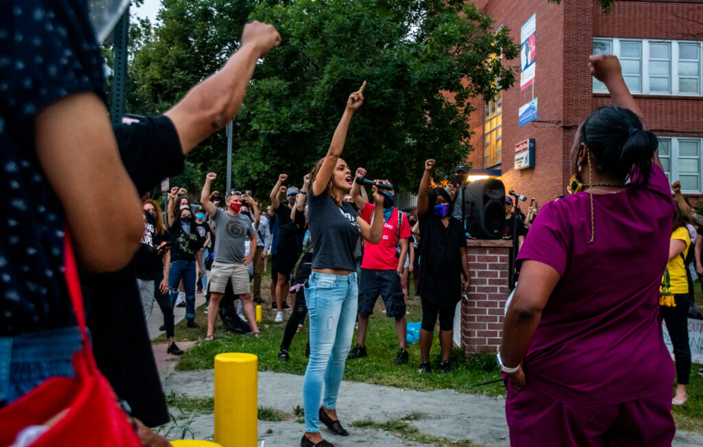 """Elisabeth Epps, founder of the Colorado Freedom Fund, leads the closing chant during the """"Protect Black Men: Colorado Action for Jacob Blake"""" gathering at Manual High School in Denver. """"It is our duty to fight for our freedom. It is our duty to win. We must love each other and support each other. We have nothing to lose but our chains,"""" chanted Epps with the crowd."""