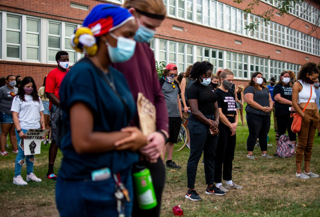 """Attendees bow their heads in prayer for Jacob Blake and victims of police brutality during the """"Protect Black Men: Colorado Action for Jacob Blake"""" gathering at Manual High School in Denver."""