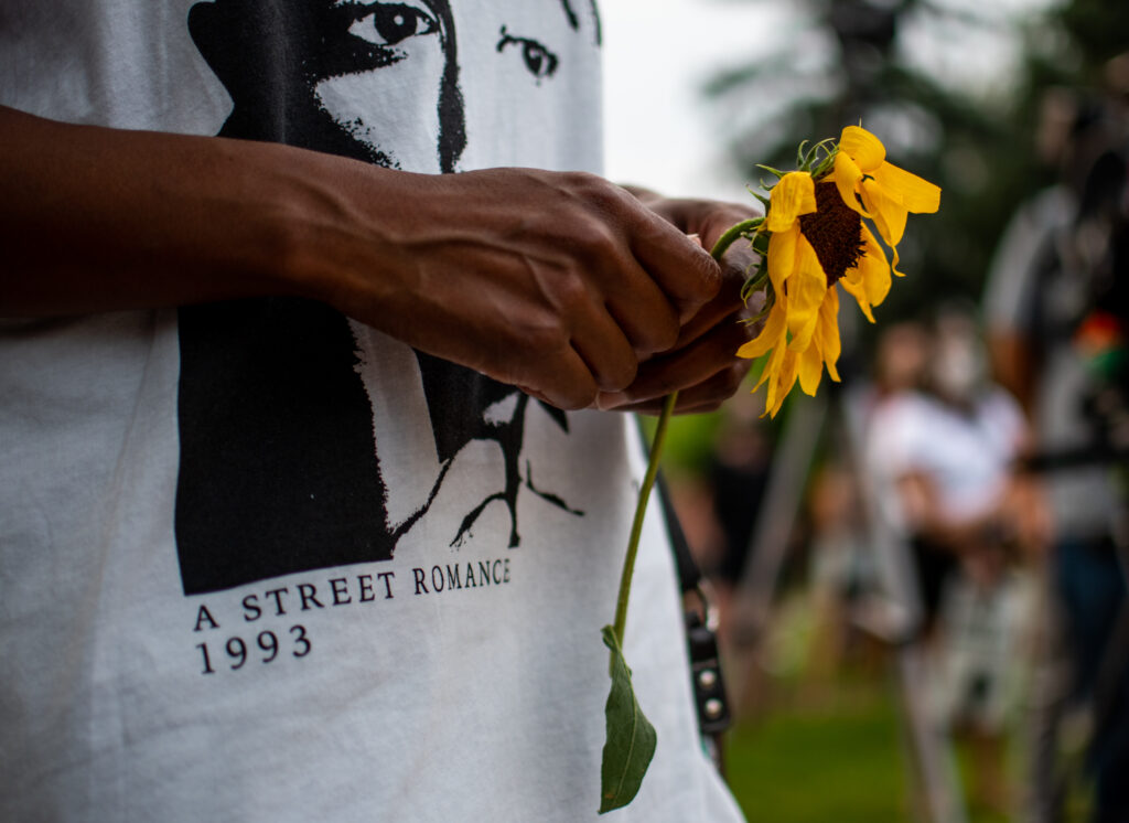 """Sheree Barbour holds a flower during the """"Protect Black Men: Colorado Action for Jacob Blake"""" gathering at Manual High School in Denver."""