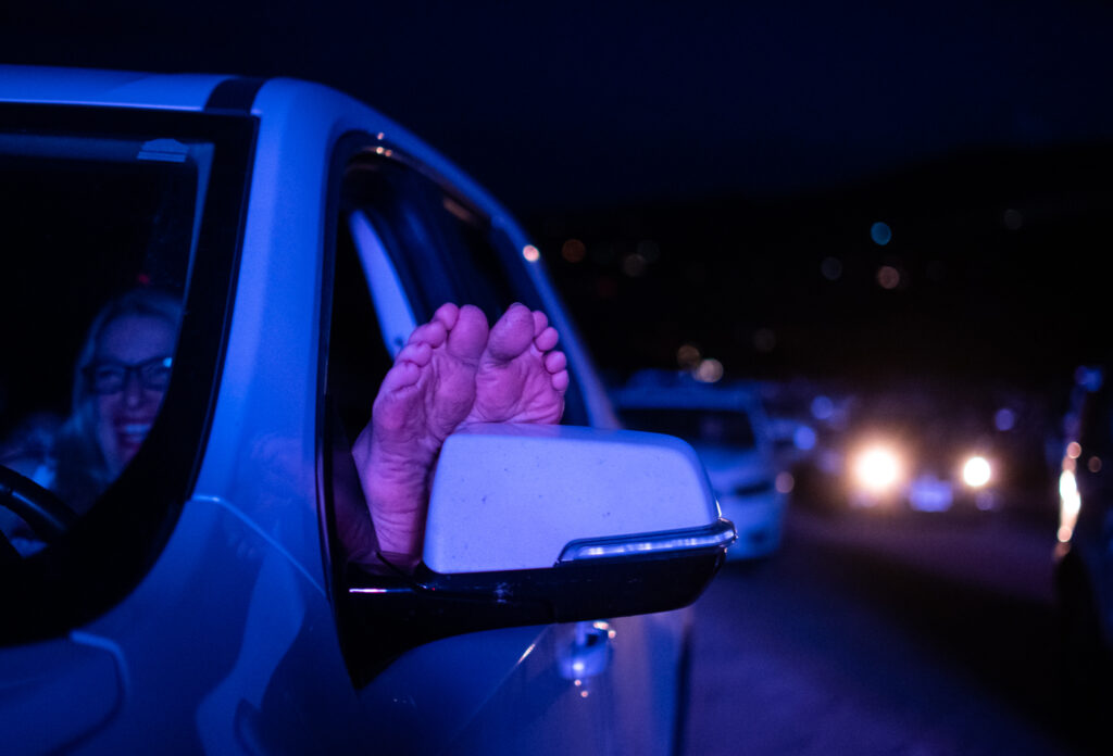 Zelinne Lizzi relaxes with her feet up during the 21st annual Film on the Rocks, drive-in edition at Red Rocks Park on Aug. 13, 2020.