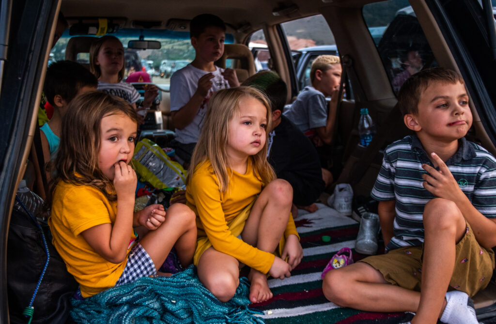 From left, Dagney Brazil, 5, Isla Abeyta, 5, and Eli Brazil, 7, watch Grease while eating snacks with their friends and siblings during the 21st annual Film on the Rocks, drive-in edition at Red Rocks Park on Aug. 13, 2020.