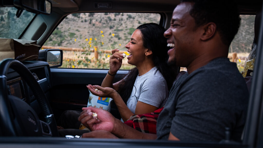 Cassie Yrigollen, center, and Golden Goodwin joke around and eat popcorn as Grease begins during the 21st annual Film on the Rocks, drive-in edition at Red Rocks Park on Aug. 13, 2020.