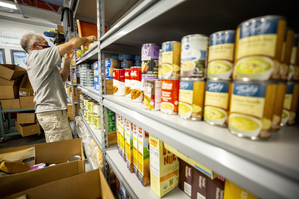 Kim Favero stacks cans at a food pantry run by West High School's alumni association. Sept. 11, 2020.
