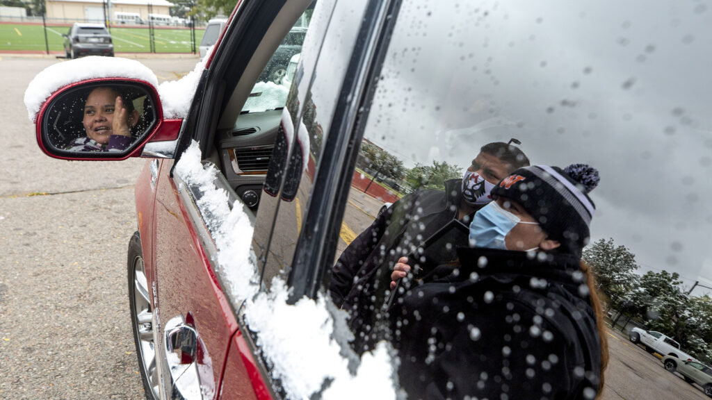 Ana Arteaga and Matias Sanchez speak with Ana Olivaria as her car is filled with food outside of West High School. Sept. 9, 2020.