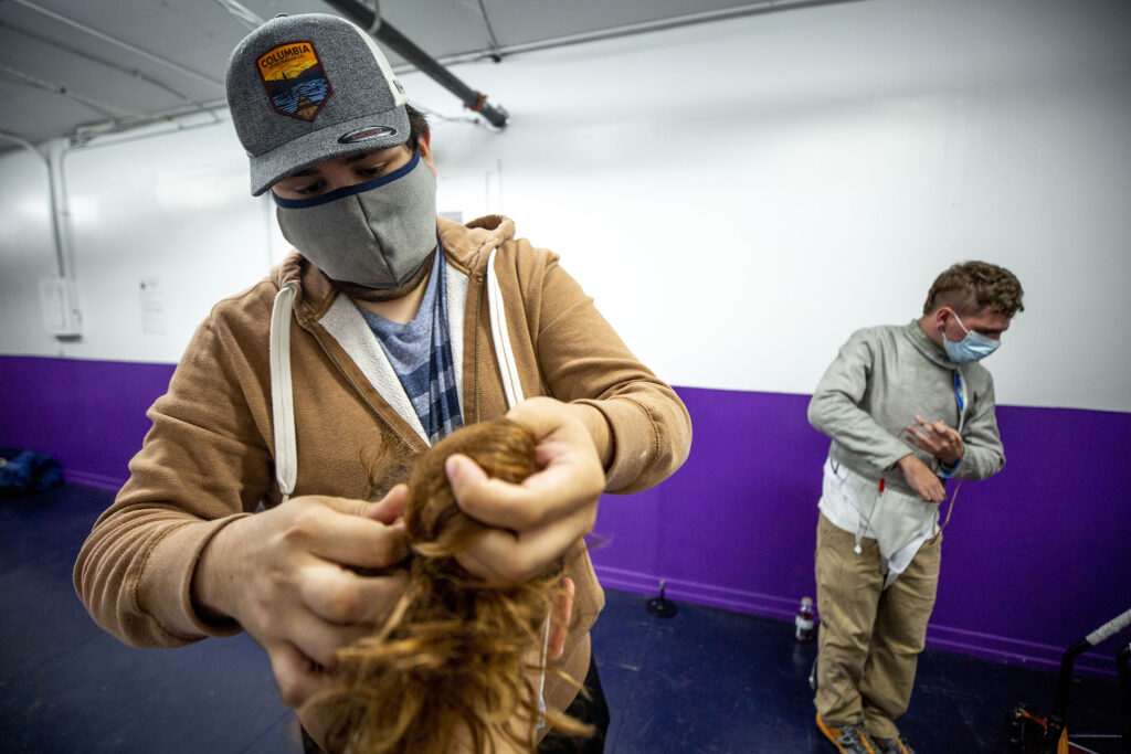 Hailey Bauer's boyfriend, Gilberto Guerra, ties up her hair before training at the Denver Fencing Center in Ruby Hill.  Sept. 10, 2020.