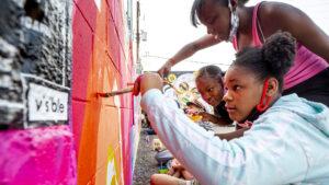 Jasmine (left to right), Jadah and Jordan Ward paint a wall during CRUSH Walls 2020 outside of Denver Central Market on Larimer Street. Sept. 18, 2020.
