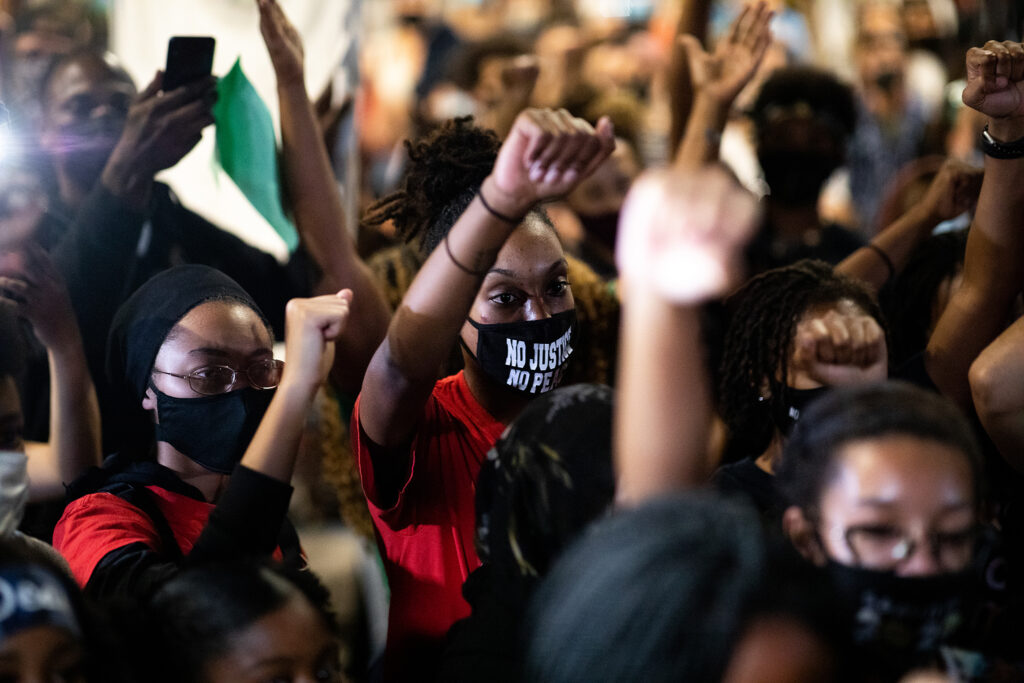 Moesha Lewis raises her fist Sept. 23 in a Denver march to rally for Breonna Taylor after a grand jury announced charges against one of the officers involved in her shooting death.
