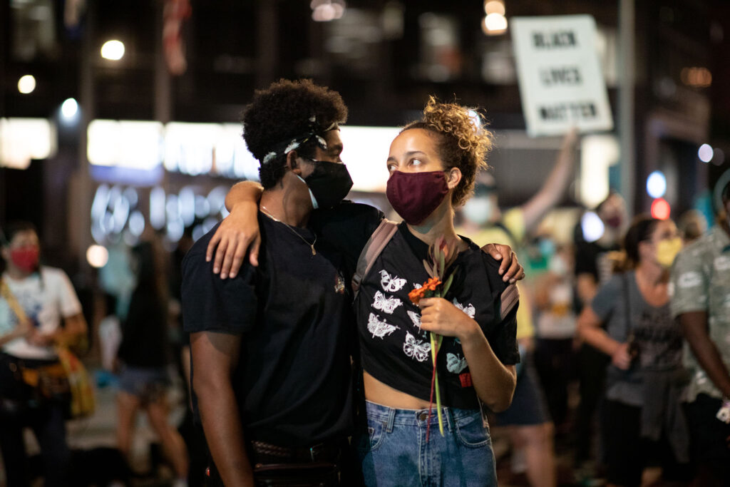 A man and woman put their arms around each other on Sept. 23 at a rally in Denver for Breonna Taylor.