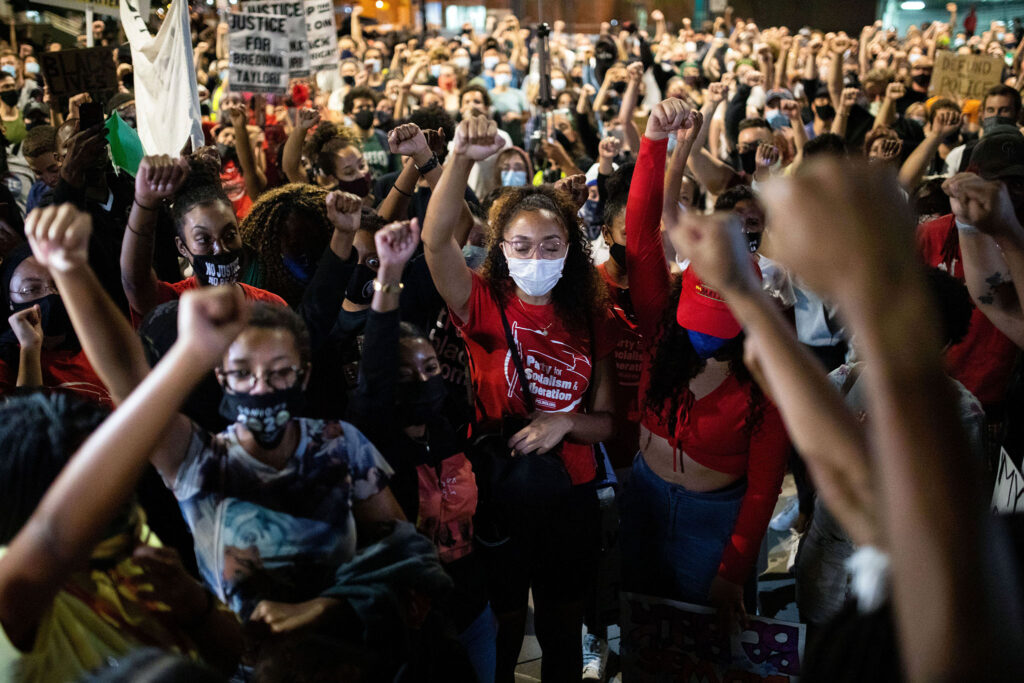 Jordan Cain, closes her eyes, as she raises her fist along with hundreds of other demonstrators during a rally for Breonna Taylor in Denver on Sept. 23.