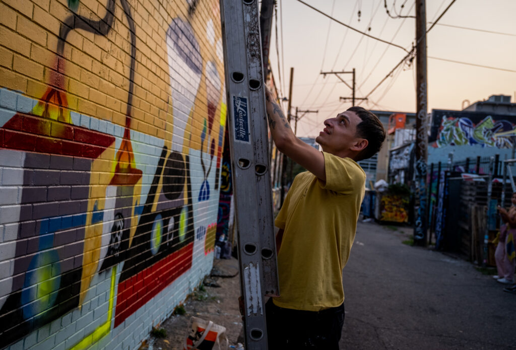 Milo moves his ladder to work on a section of his mural in a River North Art District alleyway on Sept. 17, 2020.