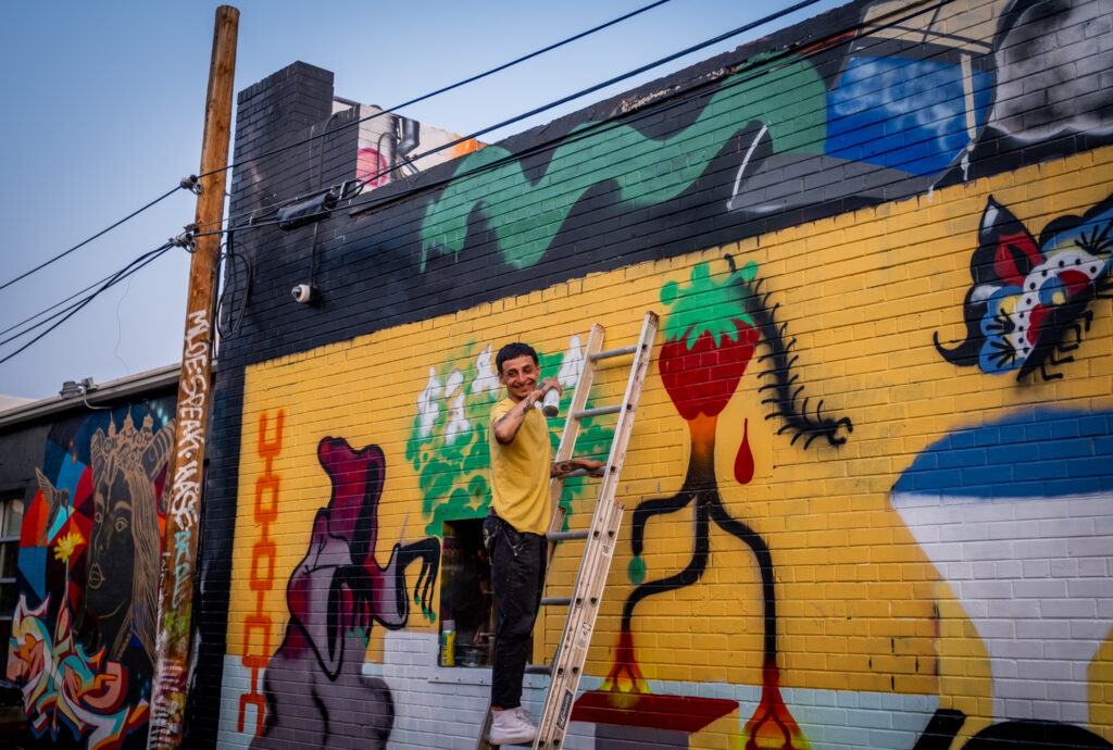 Milo laughs with friends as he paints a strawberry in a River North Art District alleyway on Sept. 17, 2020.
