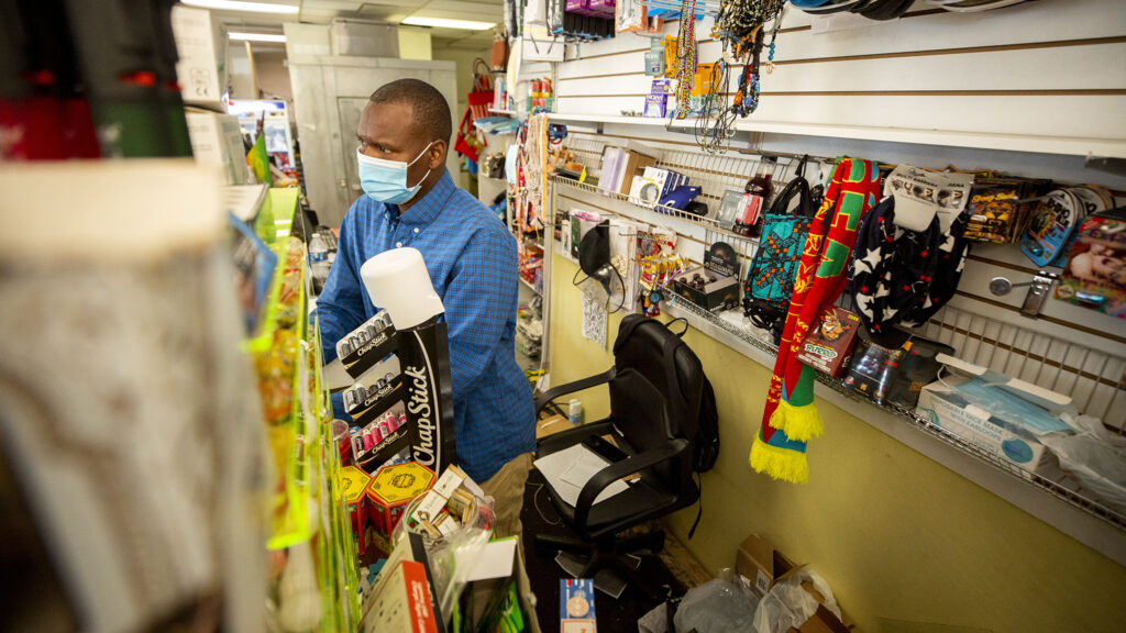 Mamadou Dia behind the counter at his store, Dia International Market, in Aurora. Oct. 1, 2020.