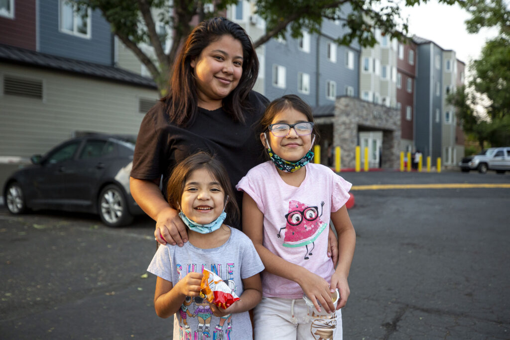 Noemy Ruano and her kids, Aleah (left) and Kimberly, stand outside of the Decatur Place Apartments where they live in Sun Valley. Oct. 1, 2020.