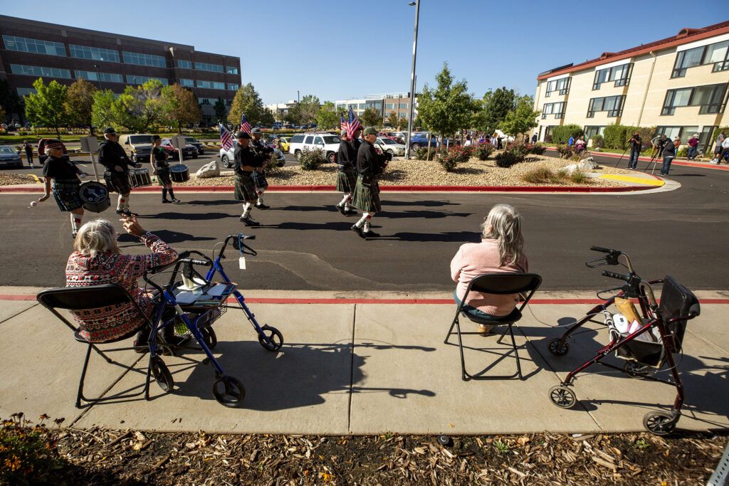 The Colorado Emerald Society Pipe Band serenades bass player Charlie Burrell on his 100th birthday, outside his home at Brookdale Lowry. Oct. 4, 2020.