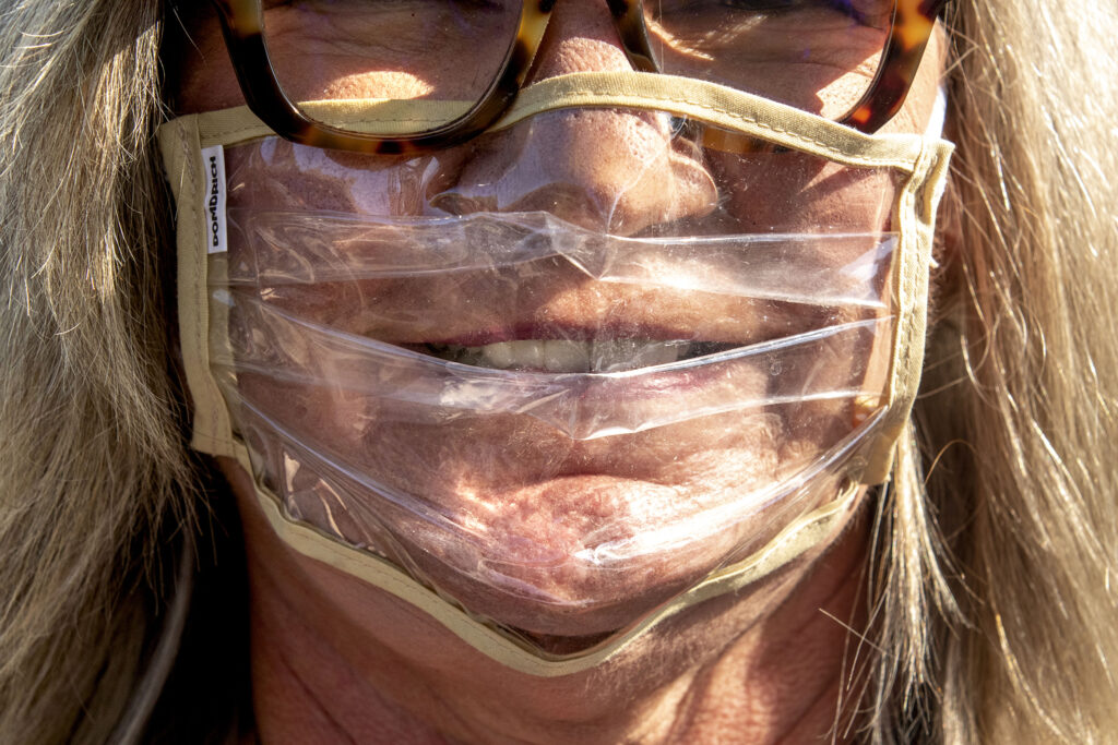 Debbie Wildrick sports a see-through mask to a rally in support of President Donald Trump at state Senate candidate Doug Townsend's home in Hale. Oct. 7, 2020.