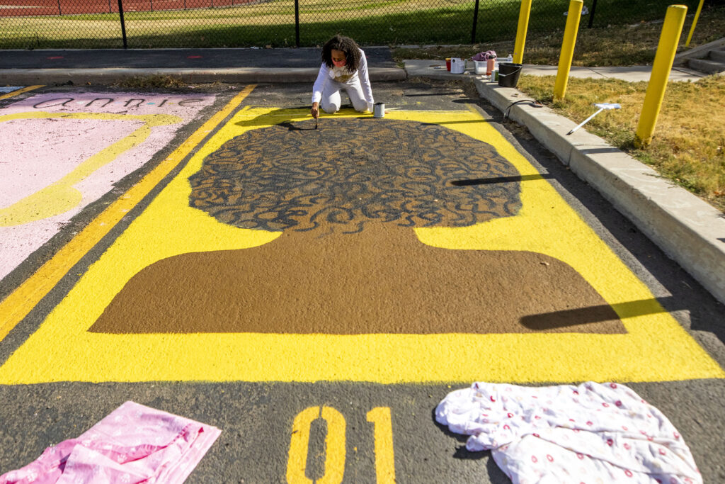 Fiona Wohannes paints her parking space, marked number one, at East High School. Oct. 16, 2020.