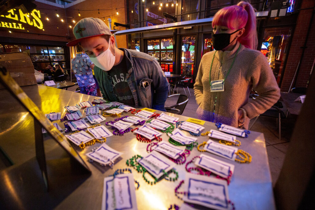 Savannah Smith and Travis M., who are visiting from Dallas, pick nametags at the start of the Denver Pub Crawl's tour of LoDo at Brother's Bar & Grill on Oct. 23, 2020.