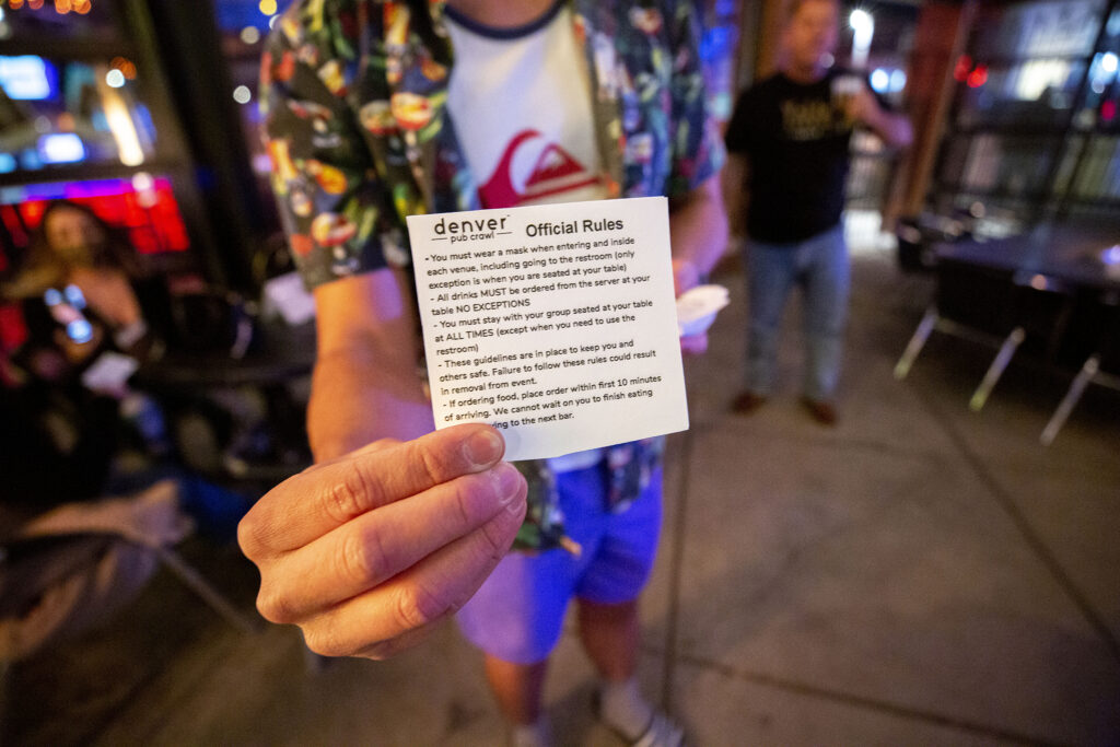 Tyler Sondag distributes official rules for his Denver Pub Crawl tour of LoDo on Oct. 23, 2020.