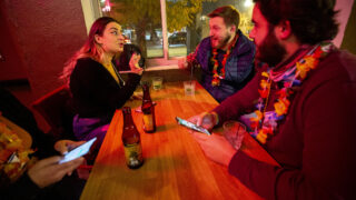 Monica Raimondi, who's visiting from Chicago, chats with New Yorkers Neil Parrello and Marshall Dickerson during a Denver Pub Crawl stop at El Chapultepec. Oct. 23, 2020.