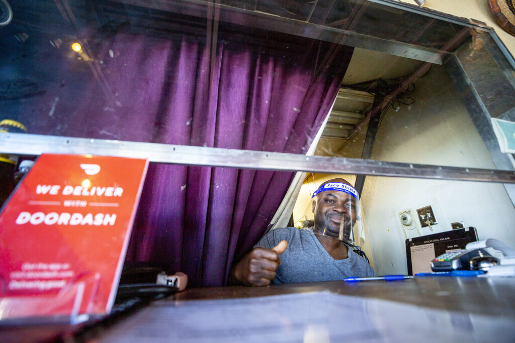 On Oct. 27, 2020, African Grill and Bar co-owner Sylvester Osei-Fordwuo peers out from behind a barrier and face shield that are new since we spoke to him in March.