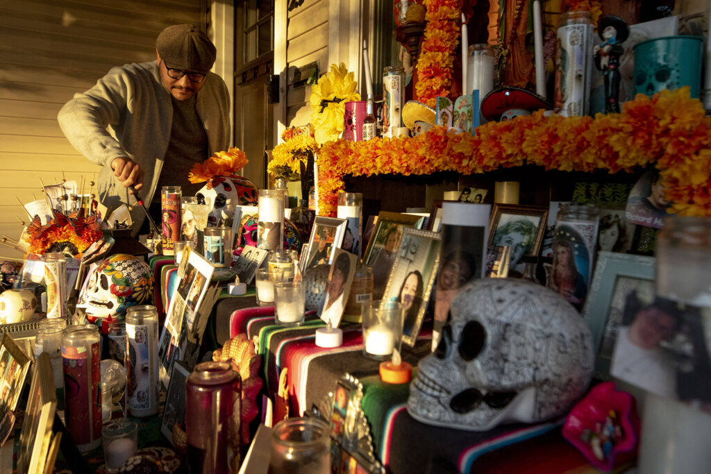 Paul Stephens lights candles for the giant ofrenda on their his porch in Harvey Park. Oct. 29, 2020.