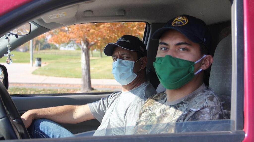 Roberto Tovar (izq.) y su hijo, David, posan para una fotografía después de hacerse la prueba de COVID-19 en un sitio comunitario el martes, 6 de octubre de 2020, en Montbello. (Esteban L. Hernandez/Denverite)