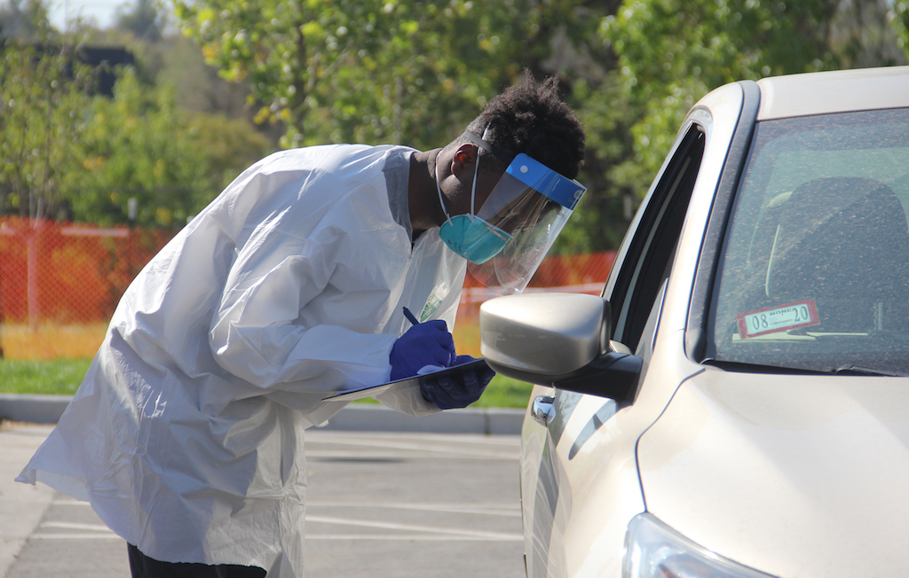 Jeran Huey takes down information before a COVID-19 exam at a coronavirus community testing site run by the city on Thursday, Oct. 1, 2020, at Paco Sanchez Park in Denver. (Esteban L. Hernandez/Denverite)