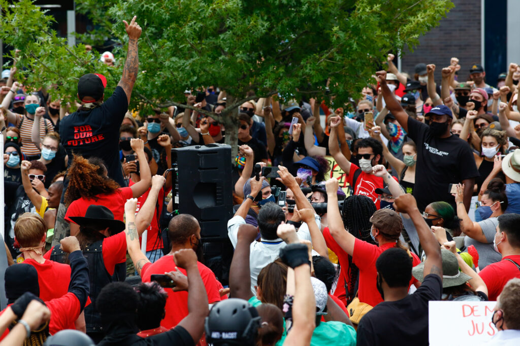 Terrance Roberts raises his arm in the air while leading protesters in calls for an end to police in Aurora, CO, August 30, 2020.  Photo by Kevin Mohatt
