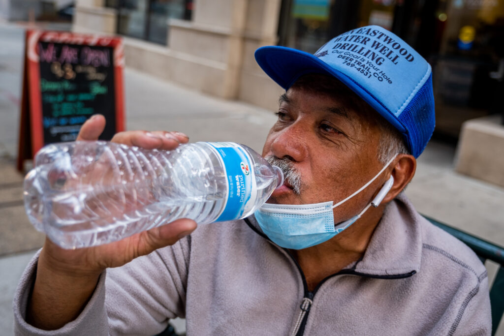 Delgado guzzles water before beginning his sales route again on Oct. 8, 2020.