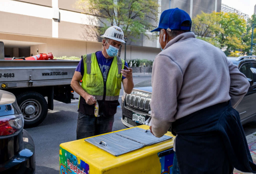 Mike Krause, a construction worker, talks with Delgado after buying a paleta in downtown Denver on Oct. 8, 2020. Krause said he frequently buys ice cream from paleteros while on the job.