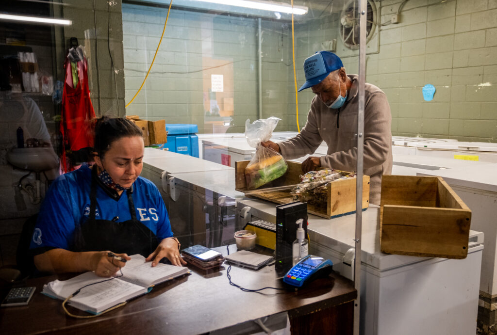 Leonor Gonzalez Romero, a Paletería Chihuahua employee, records the number of paletas Delgado sold on Oct. 8, 2020. The day was a very slow one, with around 15 paletas sold. The paletería gets half of the sales. He took home about $25, including tips.