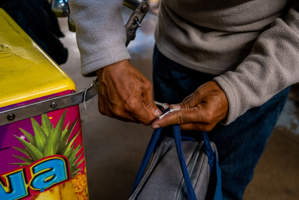 Delgado unties his bag, filled with snacks, water and a change of clothes, in the back of Paletería Chihuahua on Oct. 8, 2020.