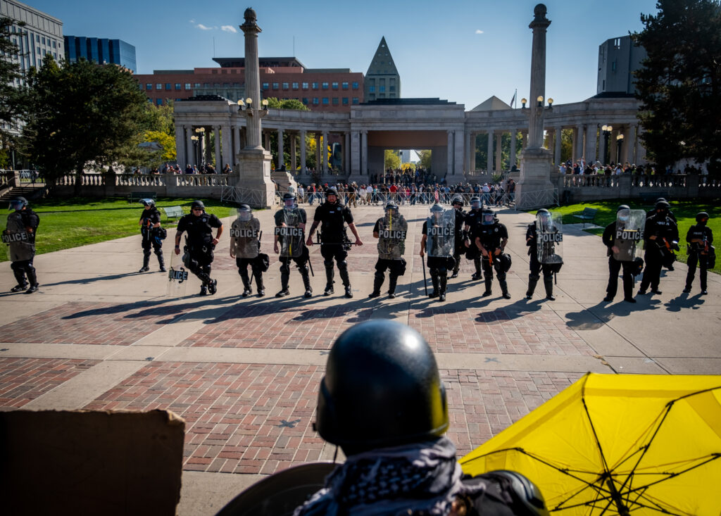 "Police officers stand between a soup drive and ""anti-fascist"" protest and a ""patriot"" rally in support of police on October 10, 2020 at Civic Center Park."