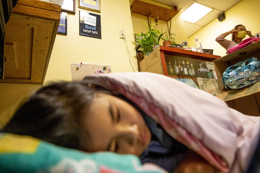 Pat (6) naps as her mom, Lek Nuntanavooth, rushes to meet a customer inside J's Noodle and Star Thai Delivery on Federal Boulevard. Oct. 28, 2020.
