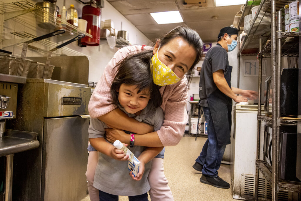 Lek Nuntanavooth embraces her daughter, Pat, after the dinner rush ended at J's Noodle and Star Thai Delivery on Federal Boulevard. Oct. 28, 2020.