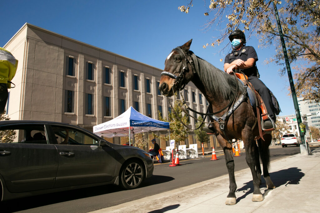 Denver Police Officer Richard Fischer was part of a mounted patrol outside Denver Elections Division headquarters where the street-level windows have been boarded up on Nov. 2, 2020, the day before Election Day.