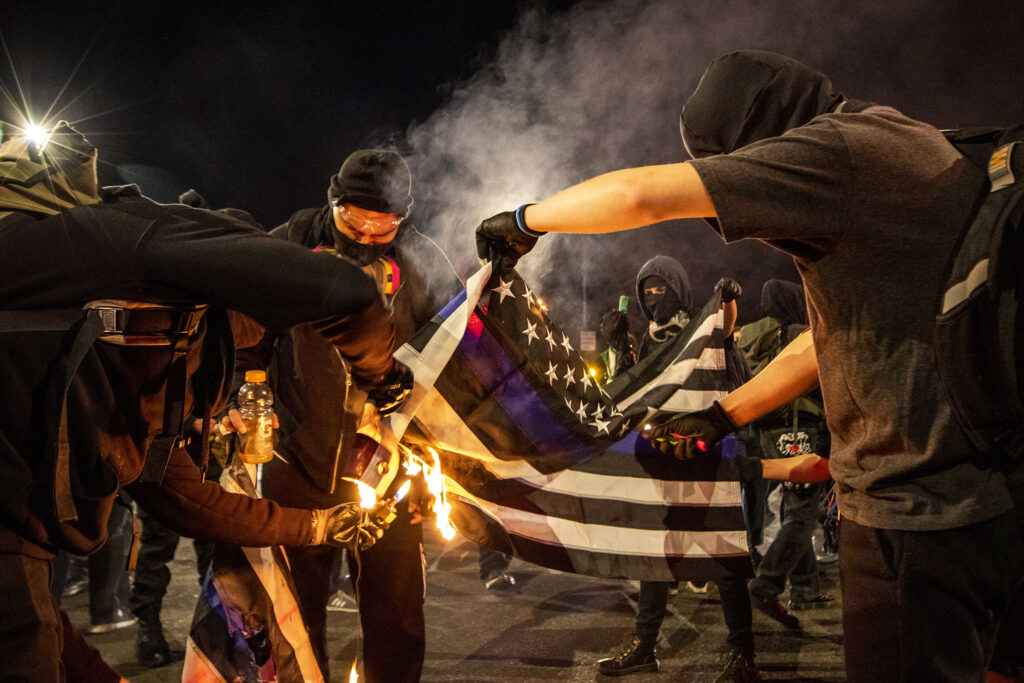 Demonstrators protesting the police and the government, regardless of who wins the election, begin their evening on East Colfax Avenue by burning a pro-police flag. Nov. 4, 2020.