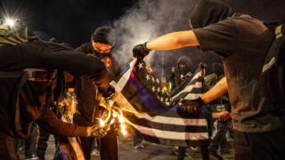 Demonstrators protesting the police and the government begin their evening on East Colfax Avenue by burning a pro-police flag. Nov. 4, 2020.
