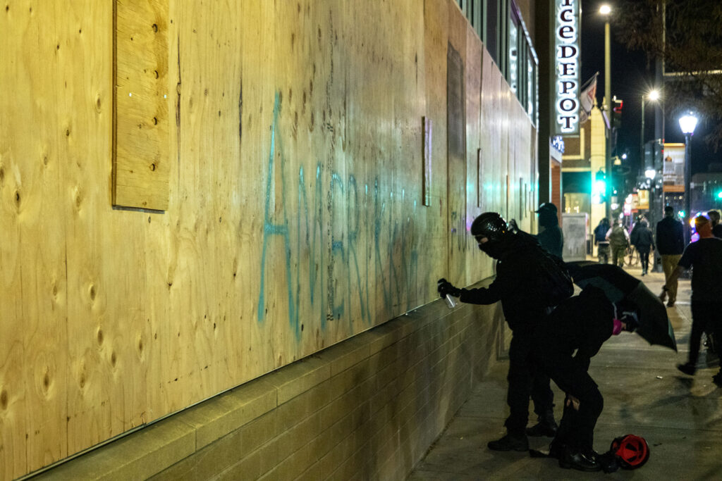 "A demonstrator writes ""Amerikkka"" on the side of a building on East Colfax Avenue during a protest against the police and the government, regardless of who wins the election. Nov. 4, 2020."