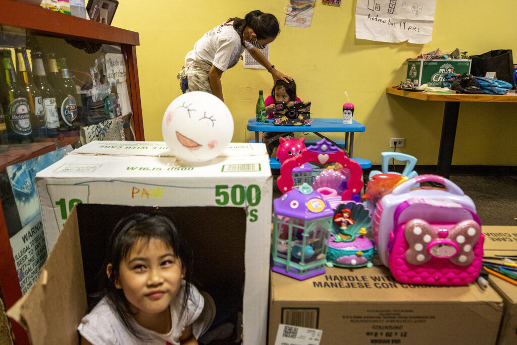 Lek Nuntanavooth checks on Pat's dinner as Pan plays in a cardboard-box fort during the evening rush at J's Noodle and Star Thai Delivery on Federal Boulevard. Nov. 8, 2020.